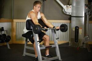 Спортсмен выполняет подъем штанги на скамье Скотта