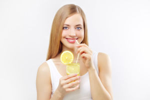 Девушка пьет воду с лимонным соком